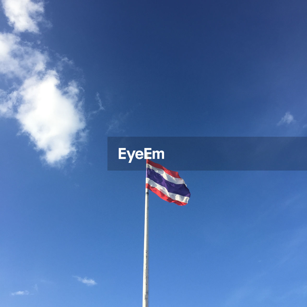 flag, sky, patriotism, low angle view, cloud - sky, blue, day, pole, nature, environment, wind, red, no people, pride, outdoors, striped, emotion, waving, independence, national icon