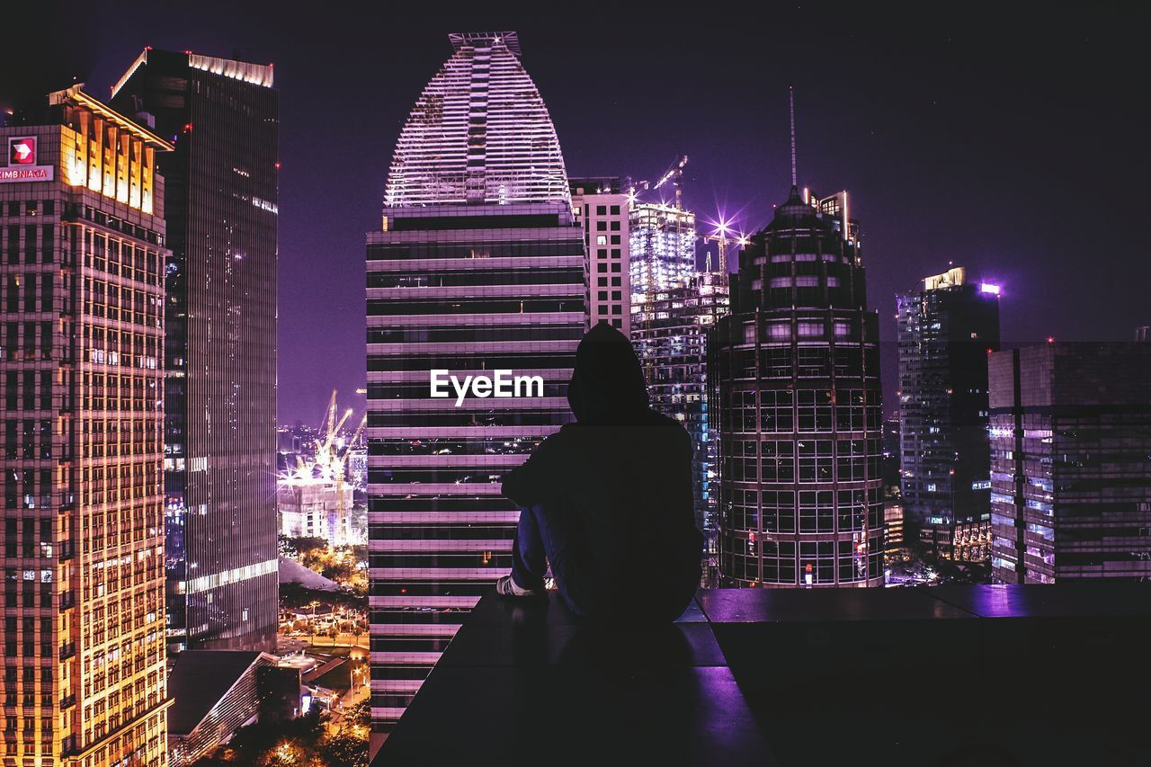night, building exterior, architecture, illuminated, skyscraper, built structure, modern, tall - high, city, real people, rear view, tourism, one person, travel destinations, outdoors, women, leisure activity, lifestyles, standing, cityscape, urban skyline, sky, people