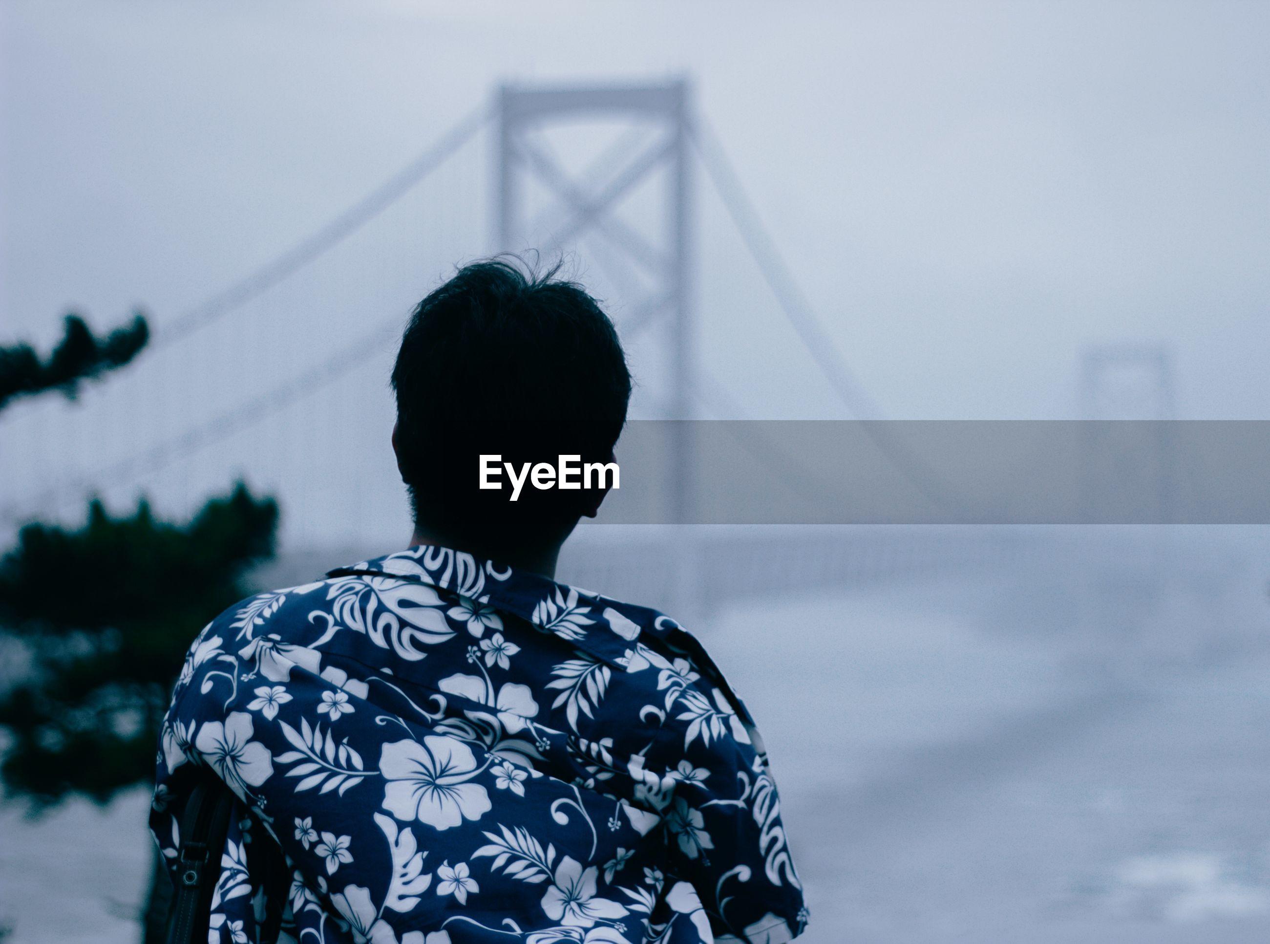 Rear view of man looking at suspension bridge