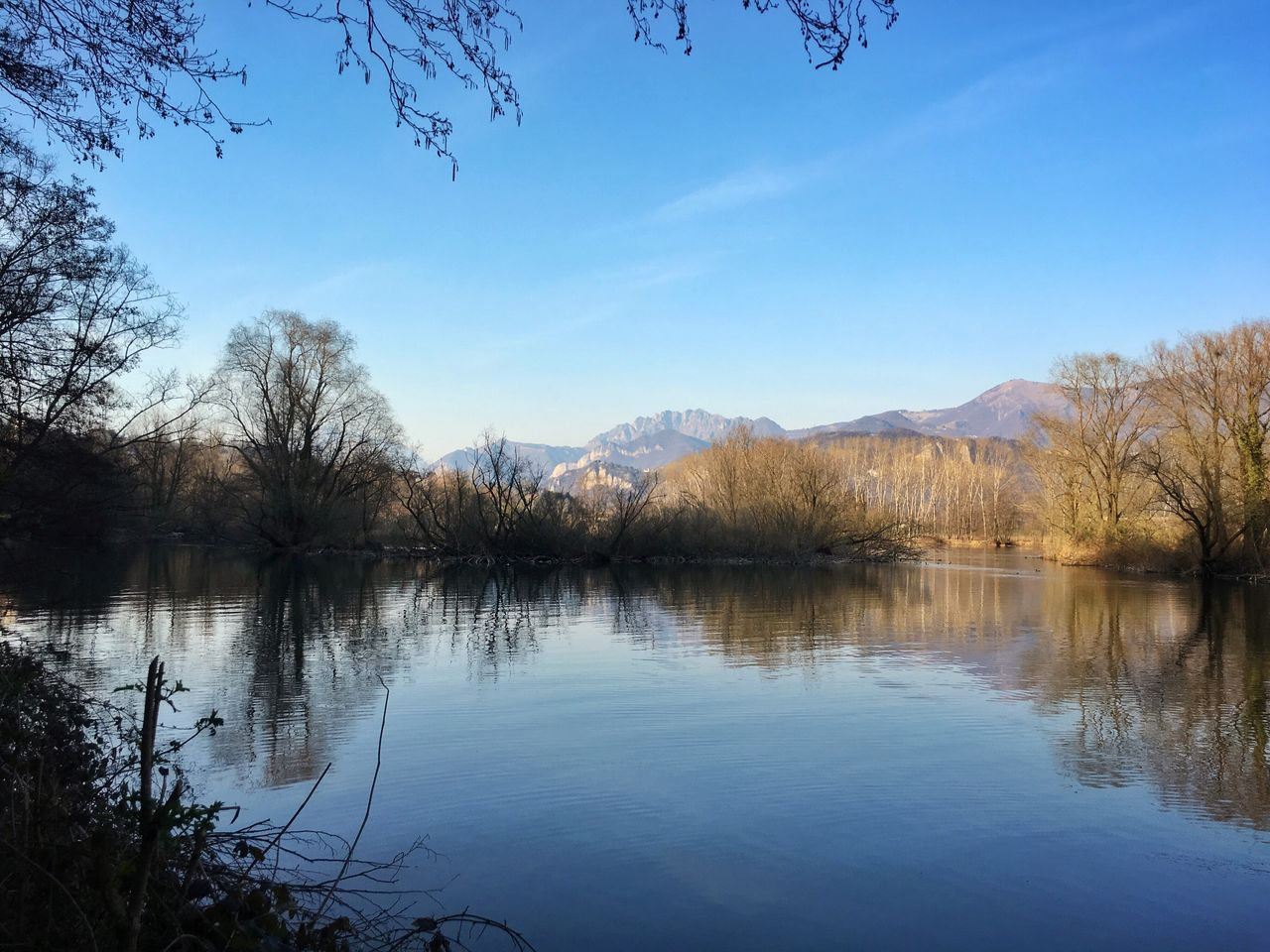 lake, reflection, water, tranquil scene, beauty in nature, tranquility, nature, scenics, mountain, tree, mountain range, outdoors, idyllic, sky, non-urban scene, no people, day, bare tree