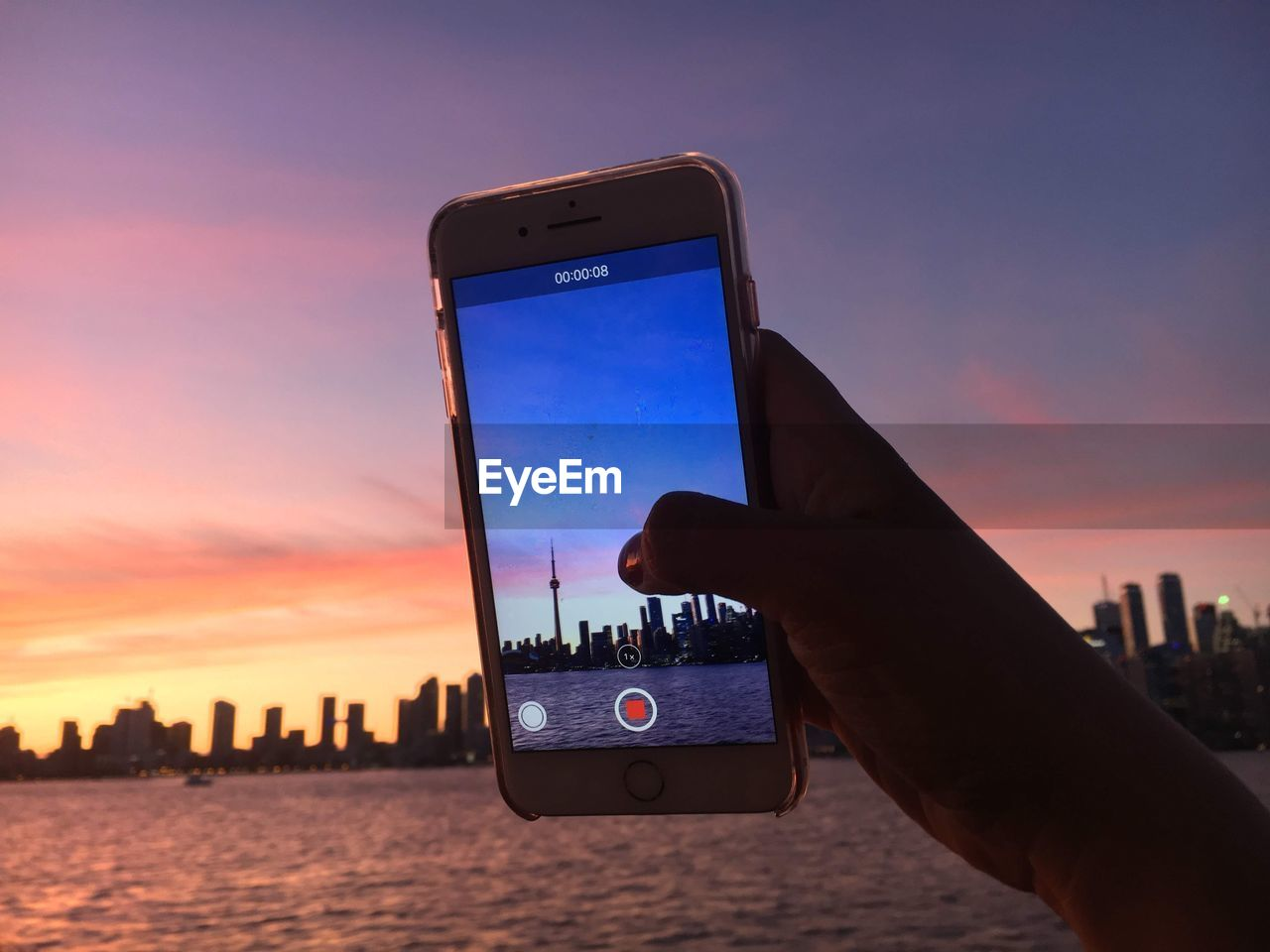 wireless technology, human hand, smart phone, hand, sunset, technology, holding, photography themes, one person, portable information device, sky, communication, mobile phone, water, human body part, connection, photographing, real people, screen, personal perspective, outdoors, cityscape, finger