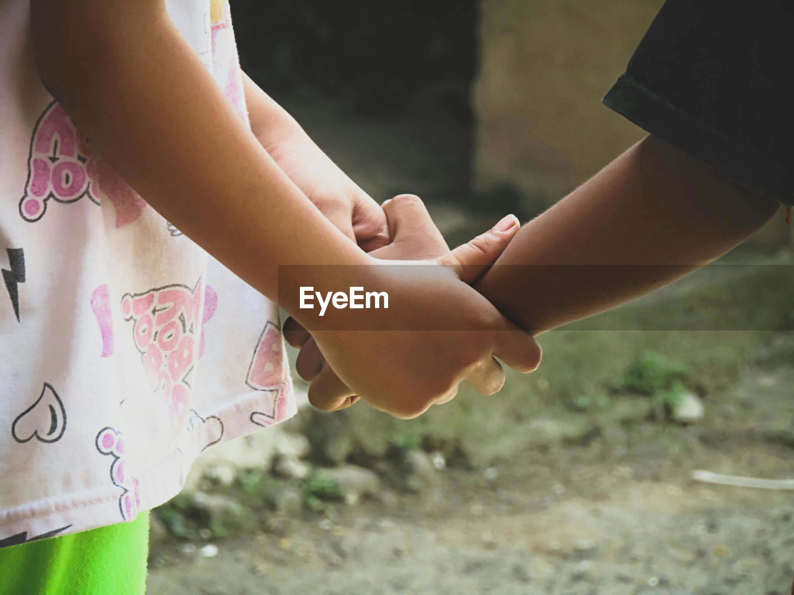 Close-up of children holding hands outdoors