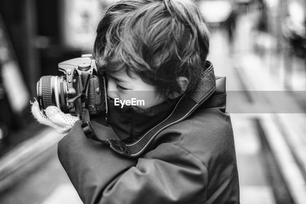 Close-up of boy holding camera