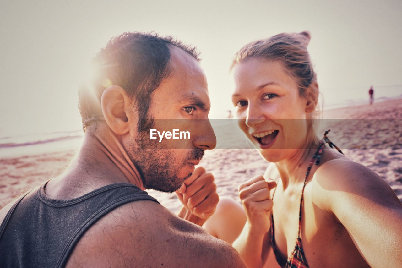 two people, beach, togetherness, leisure activity, real people, outdoors, vacations, headshot, young adult, young women, sunlight, sand, day, young men, sea, love, lifestyles, happiness, portrait, clear sky, looking at camera, sky, bonding, smiling, nature, close-up