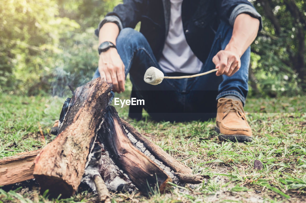Low Section Of Man Heating Marshmallow On Campfire On Field