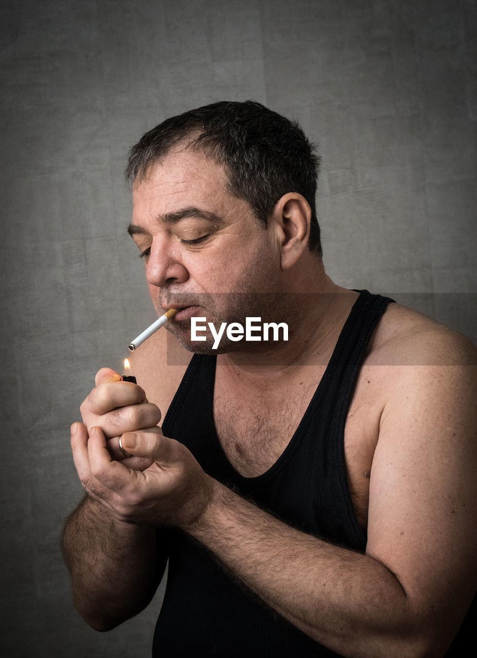 Man Smoking Against Wall