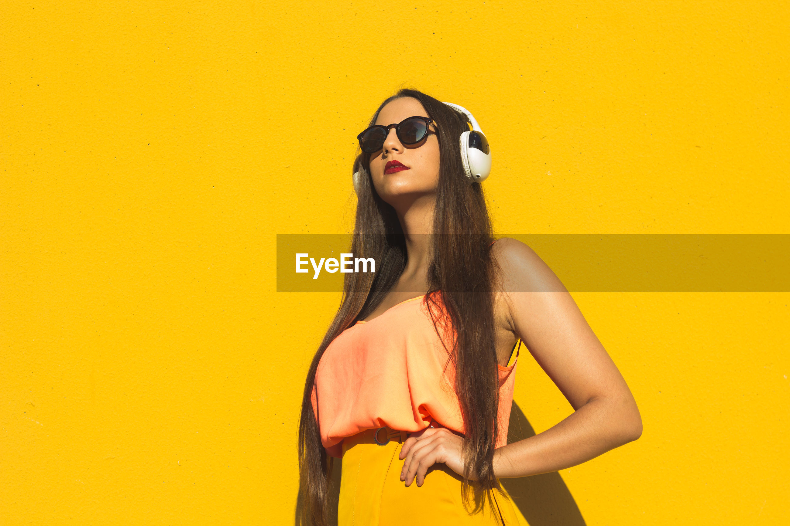 Young woman wearing sunglasses while listening music against yellow background