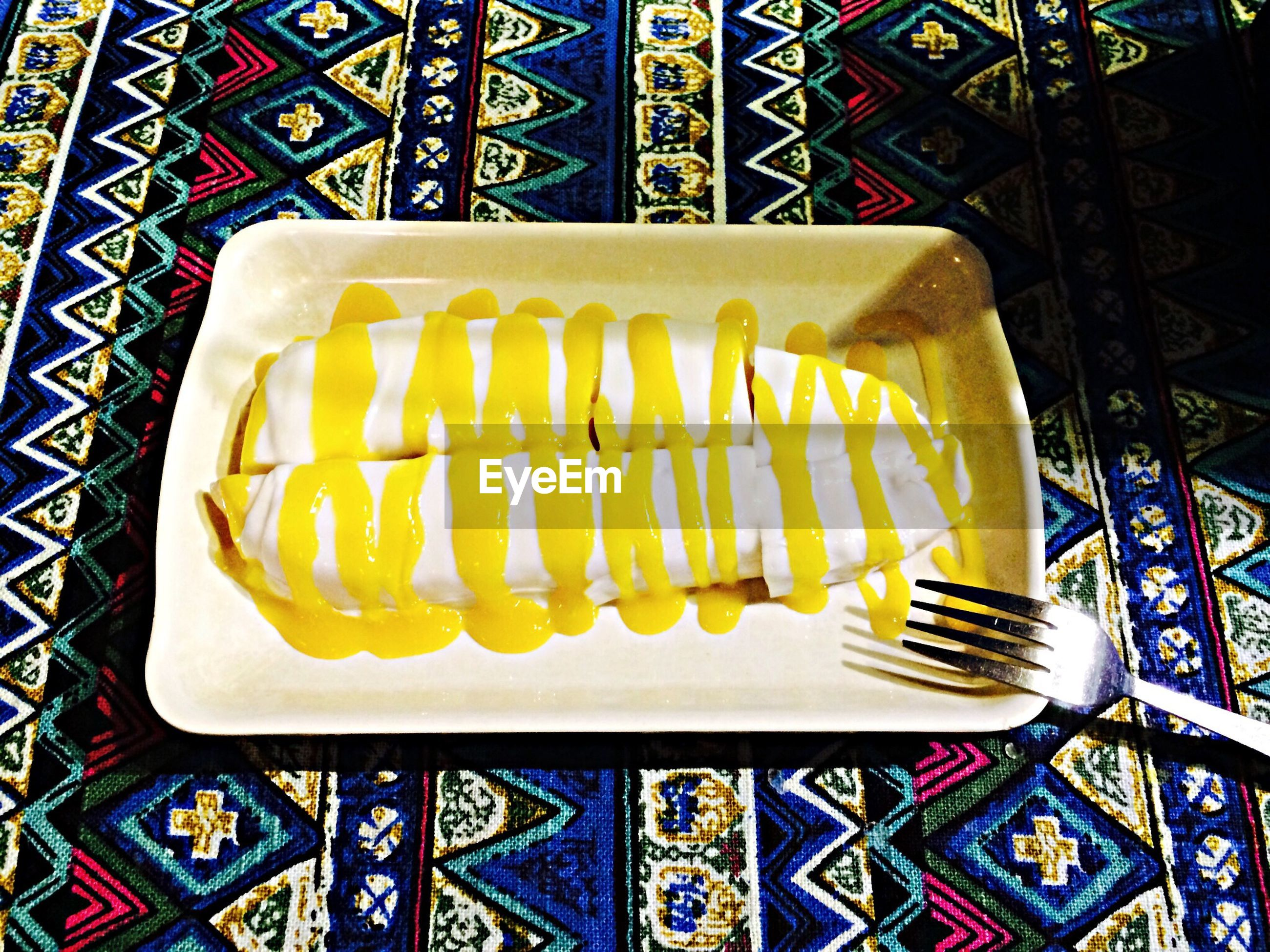 indoors, food and drink, still life, food, high angle view, table, yellow, pattern, close-up, sweet food, freshness, no people, plate, ready-to-eat, unhealthy eating, directly above, design, indulgence, dessert, tablecloth