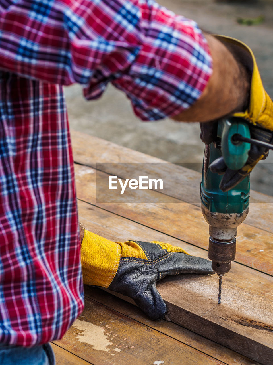 Midsection of man drilling in wood on table