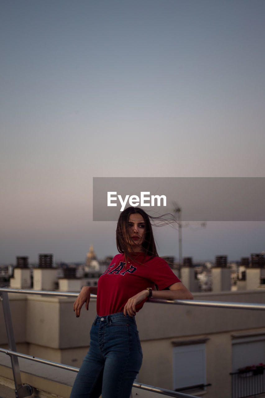 sky, one person, real people, lifestyles, architecture, standing, leisure activity, three quarter length, young adult, built structure, building exterior, casual clothing, sunset, railing, focus on foreground, portrait, young women, front view, outdoors, hairstyle, beautiful woman, cityscape