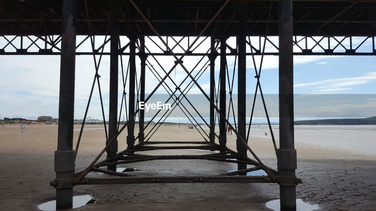 Underneath View Of Pier At Beach Against Sky