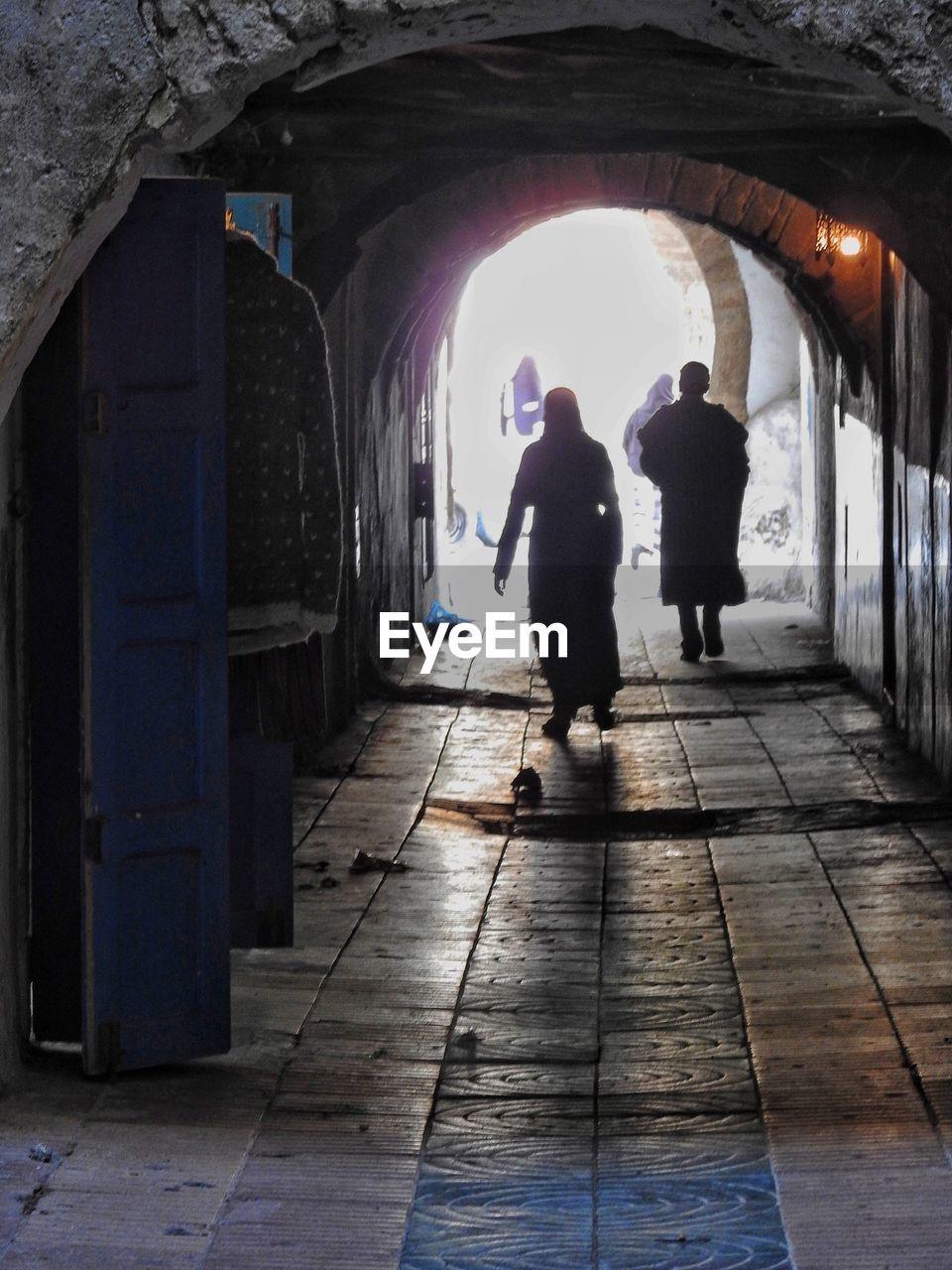 SILHOUETTE PEOPLE WALKING IN TUNNEL