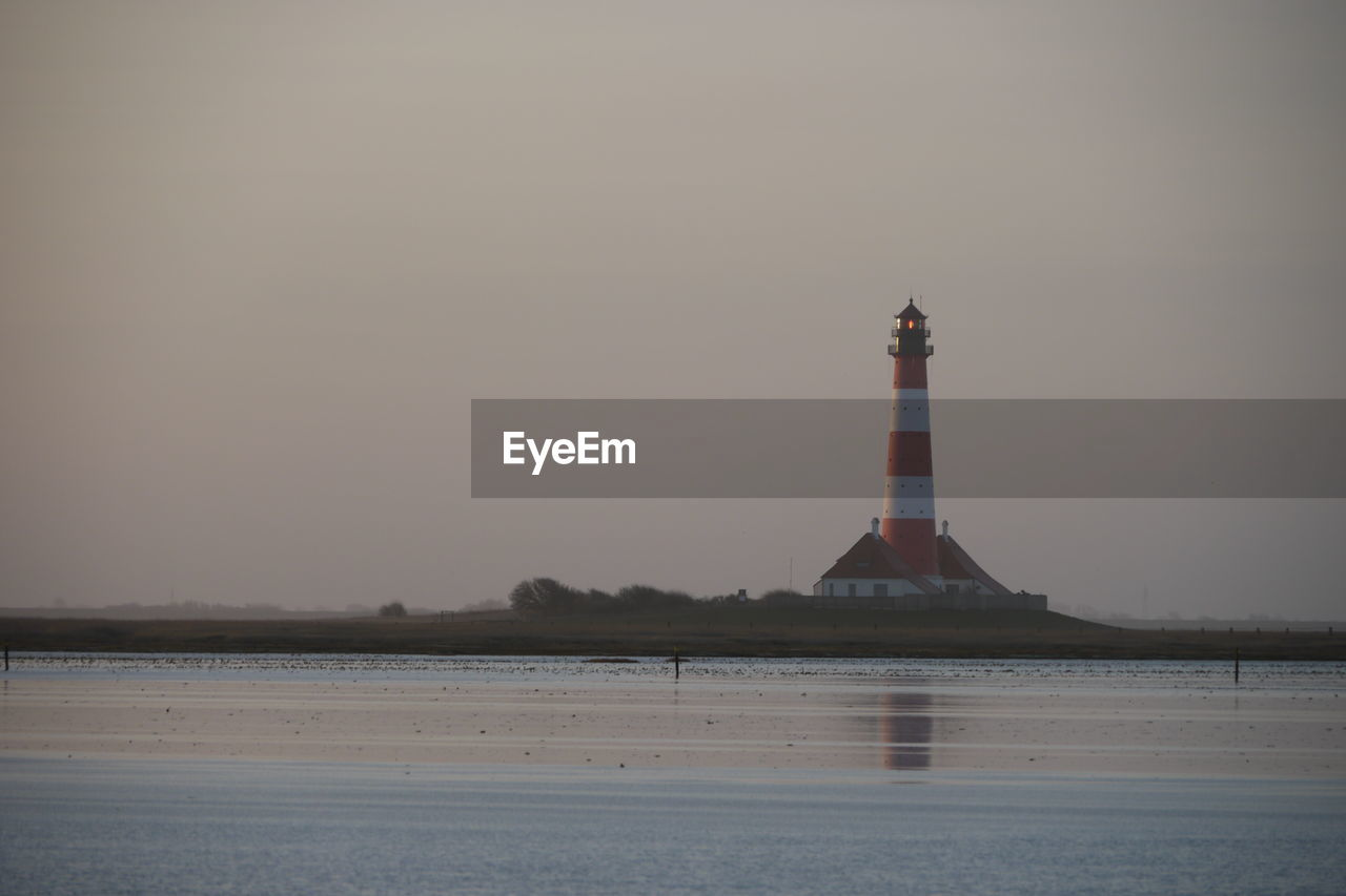 lighthouse, architecture, sea, water, guidance, safety, nature, direction, outdoors, tranquility, no people, waterfront, night, sunset, built structure, sky, beauty in nature, building exterior