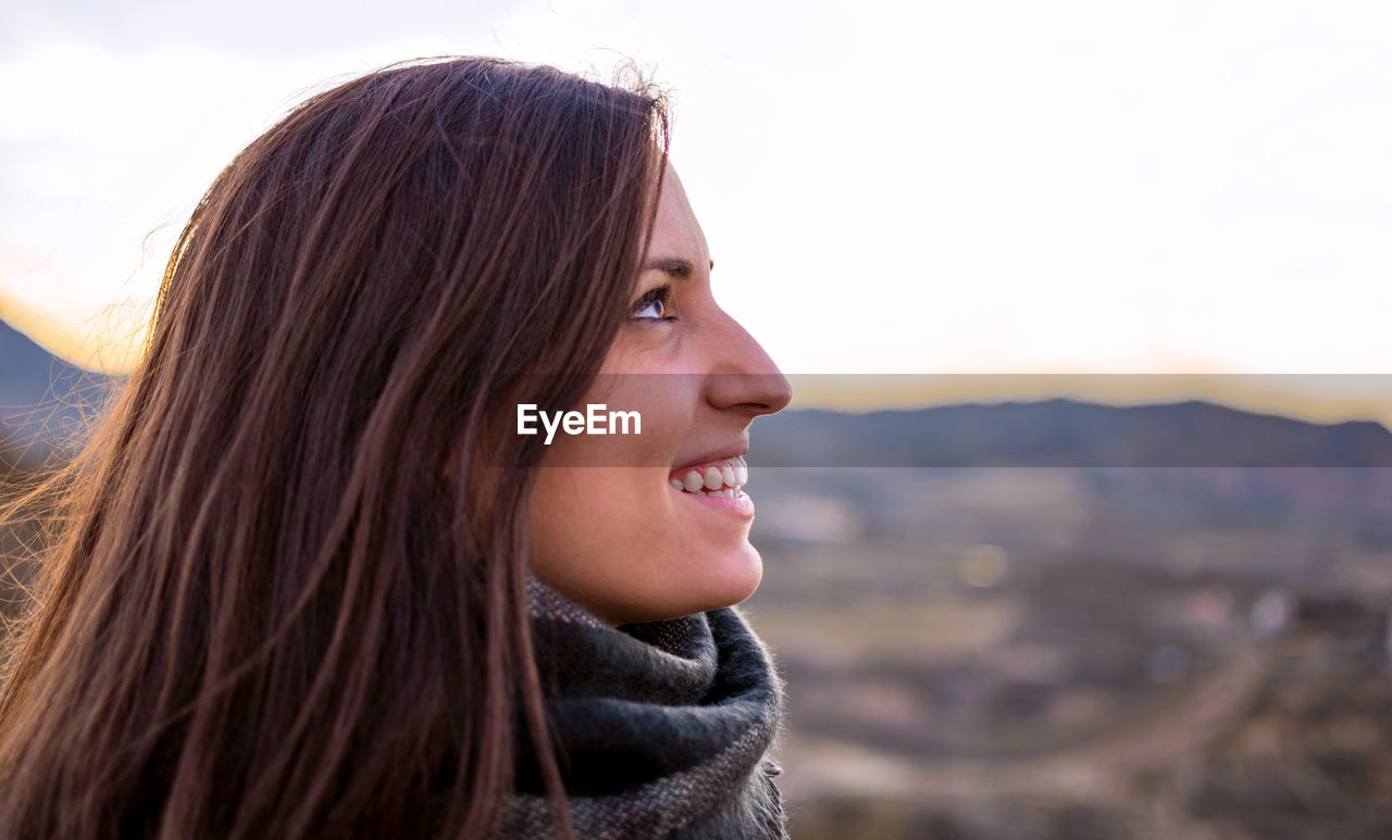 Close-up of smiling young woman looking away against sky