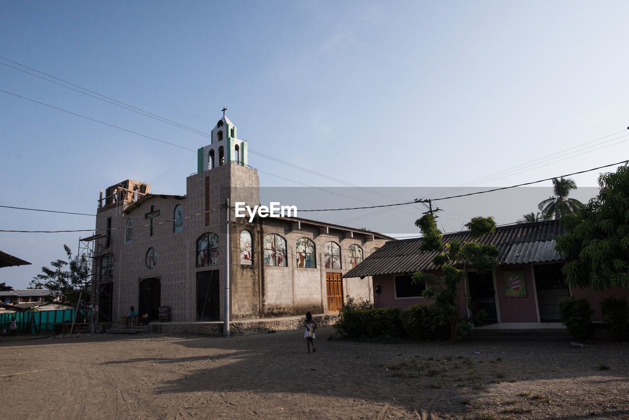 architecture, built structure, building exterior, building, sky, nature, religion, clear sky, place of worship, cable, residential district, city, belief, day, spirituality, house, old, sunlight, electricity, clock