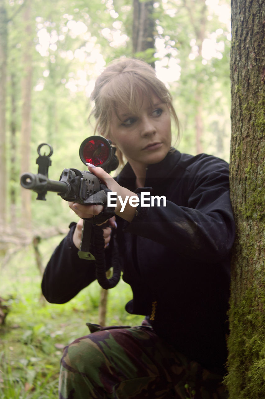 Young Woman With Sniper By Tree At Forest