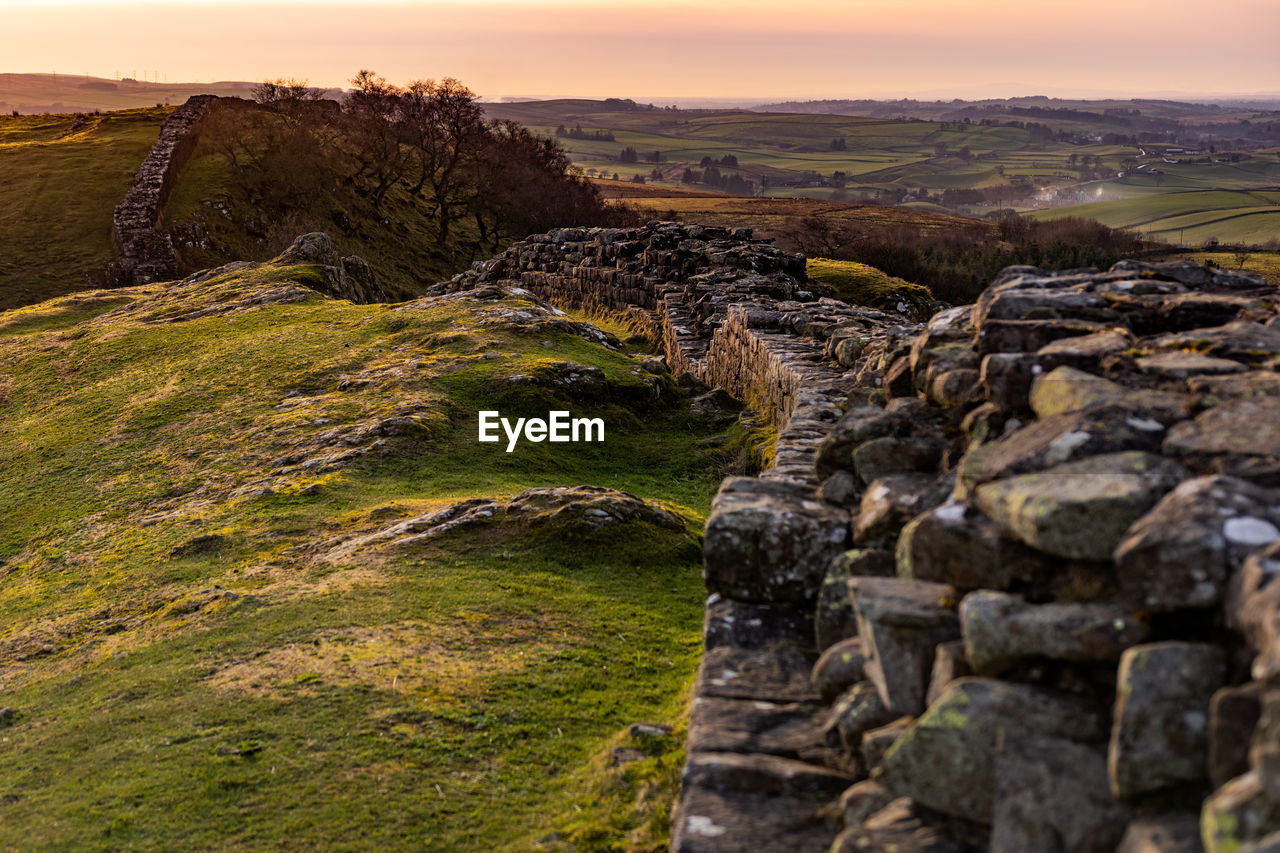 sky, environment, rock, sunset, beauty in nature, tranquility, tranquil scene, solid, scenics - nature, nature, landscape, no people, grass, rock - object, plant, land, non-urban scene, field, day, idyllic