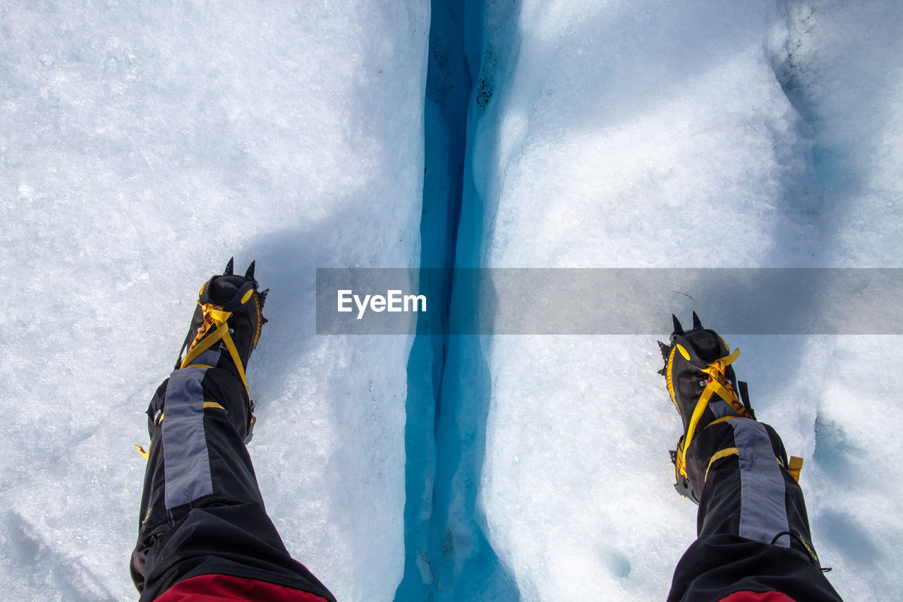 Low Section Of Person Wearing Crampon Shoe On Snowy Field