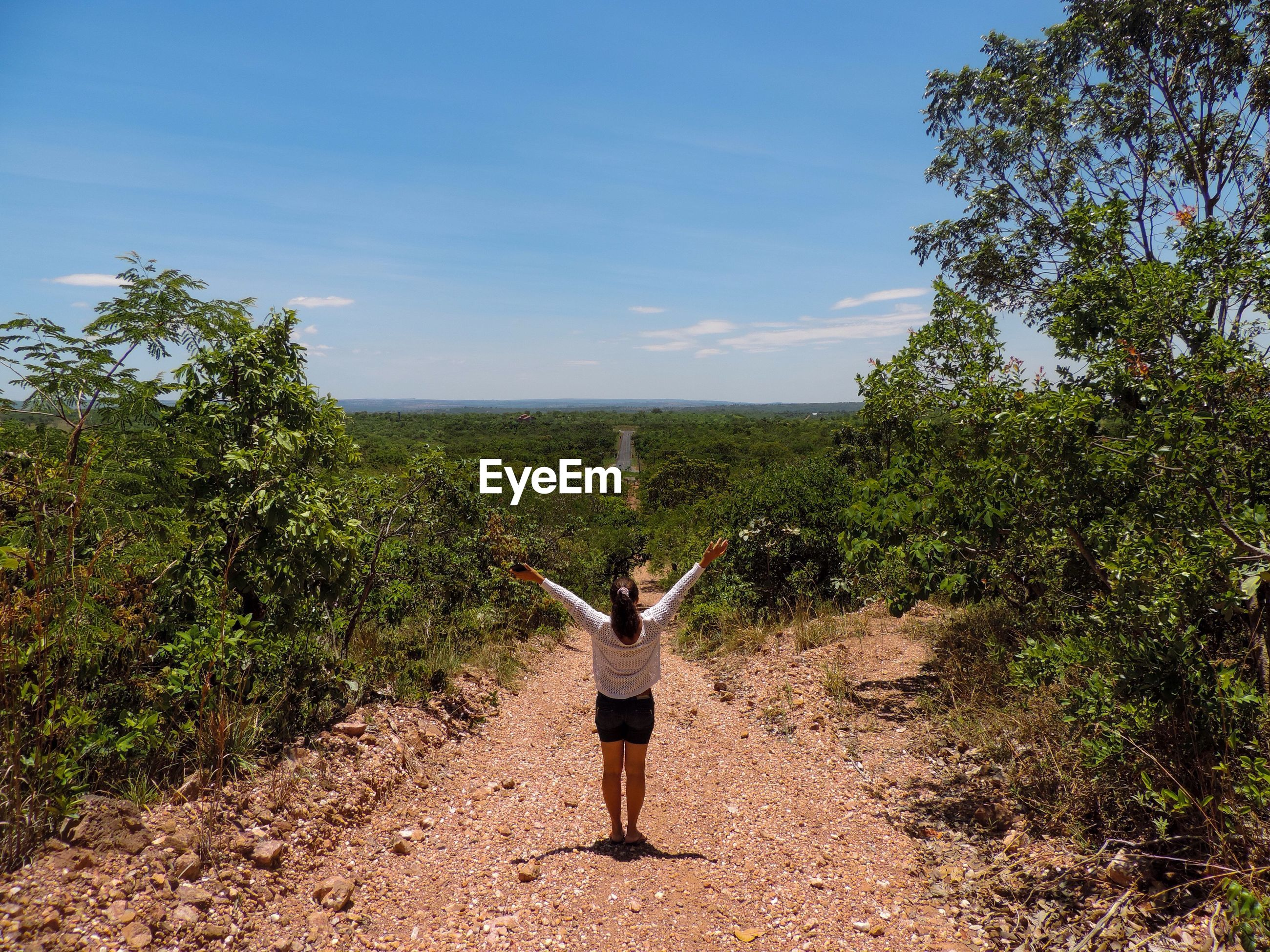 Rear view full length of woman with arms raised amidst trees on dirt road