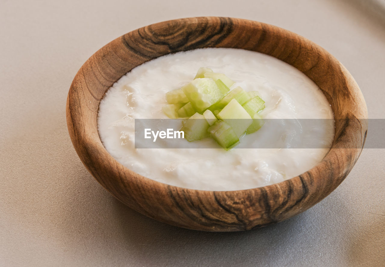 Close-up of cucumber and yogurt in wooden bowl on table