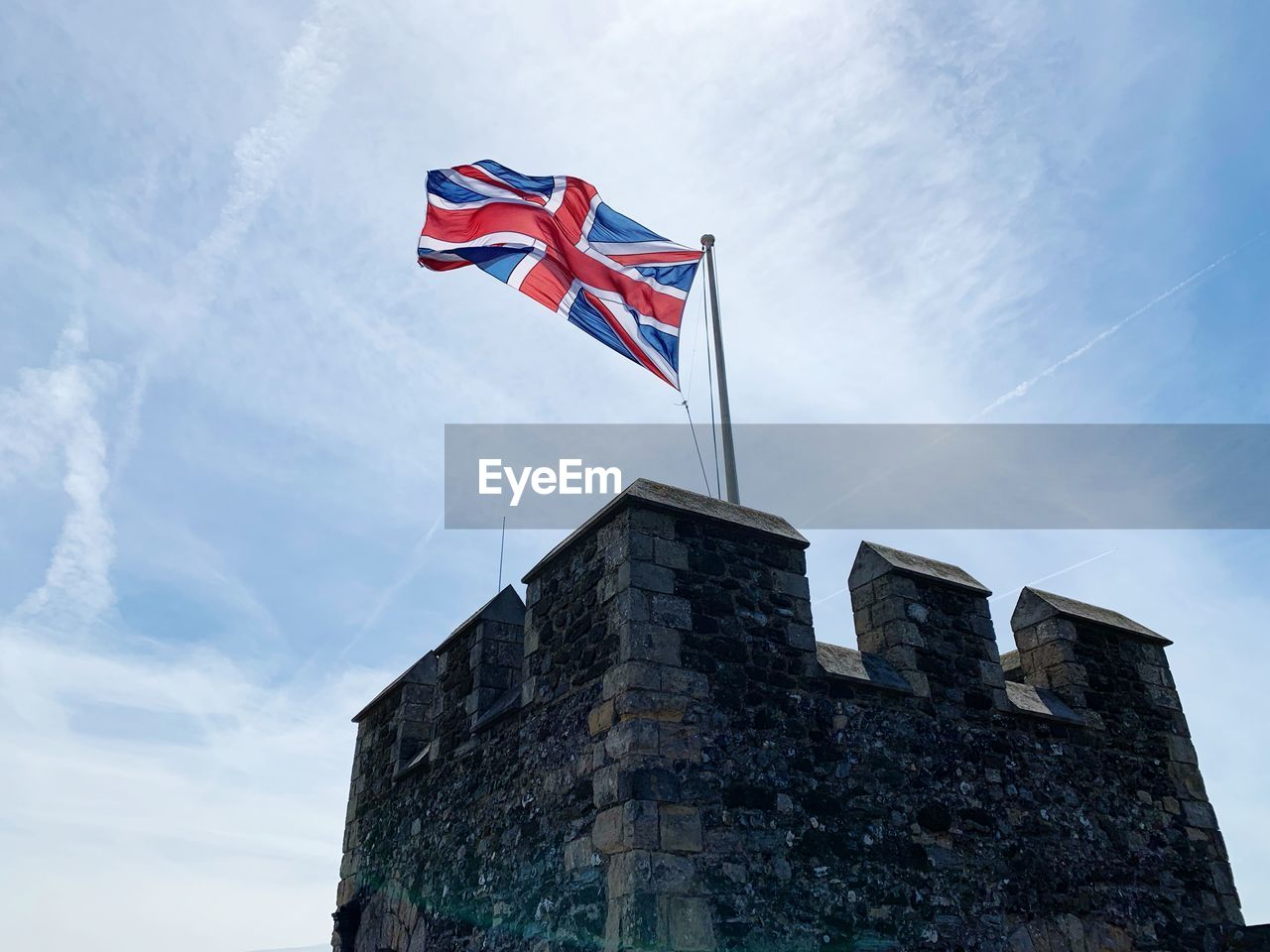 low angle view, sky, patriotism, flag, architecture, built structure, building exterior, cloud - sky, day, nature, building, no people, pride, outdoors, waving, the past, history, wind, stone wall, independence, national icon