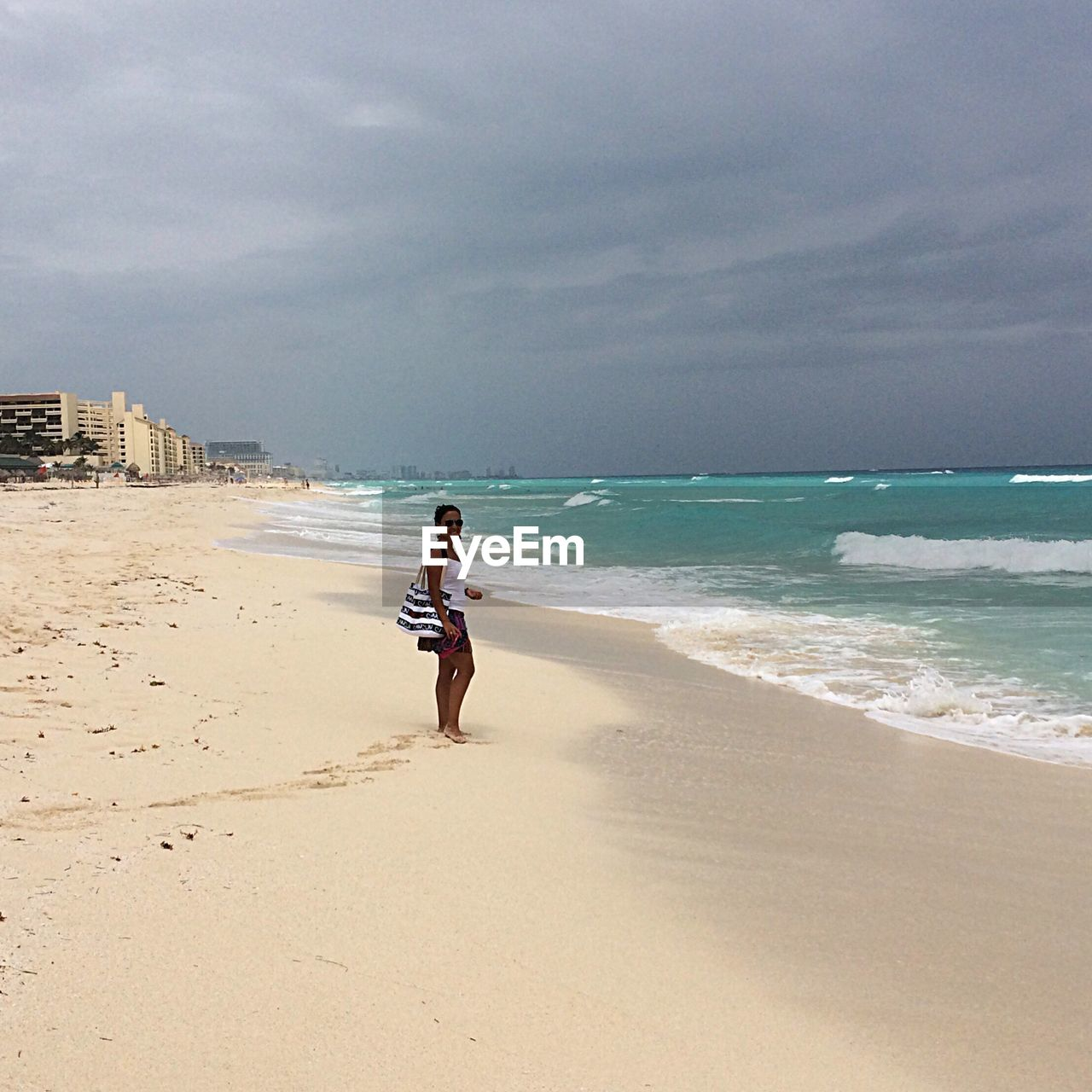 beach, sea, sand, shore, one person, full length, nature, real people, water, horizon over water, sky, scenics, beauty in nature, rear view, walking, lifestyles, leisure activity, day, outdoors, standing, vacations, wave, motion, tranquility, ankle deep in water, young adult, women, young women, people
