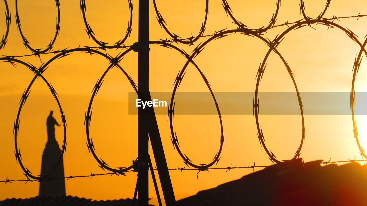Close-up of spiral razor wire fence at sunset