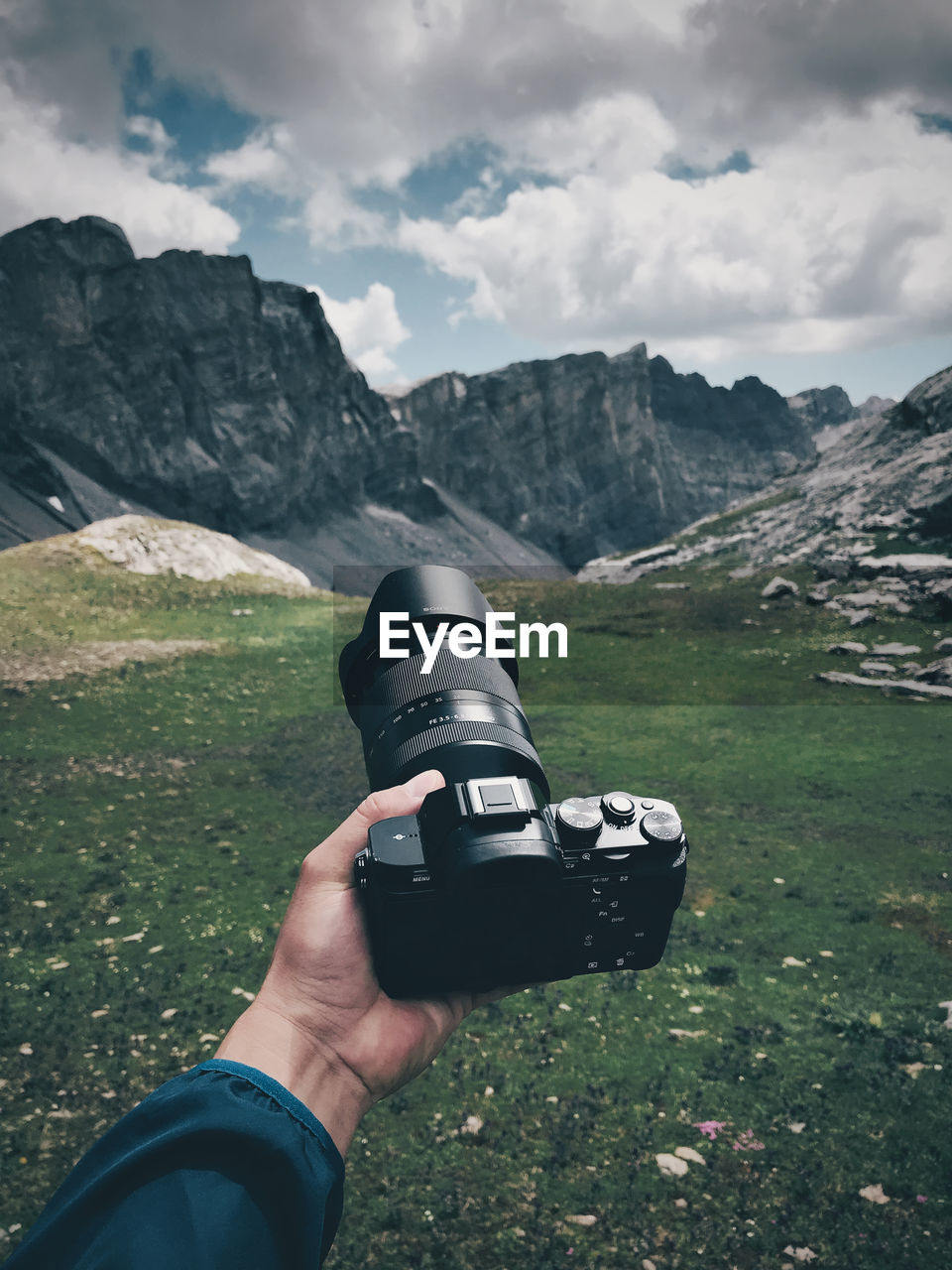 human hand, mountain, hand, photography themes, one person, scenics - nature, human body part, real people, personal perspective, holding, sky, nature, cloud - sky, non-urban scene, activity, landscape, mountain range, day, leisure activity, environment, body part, outdoors, digital camera, finger