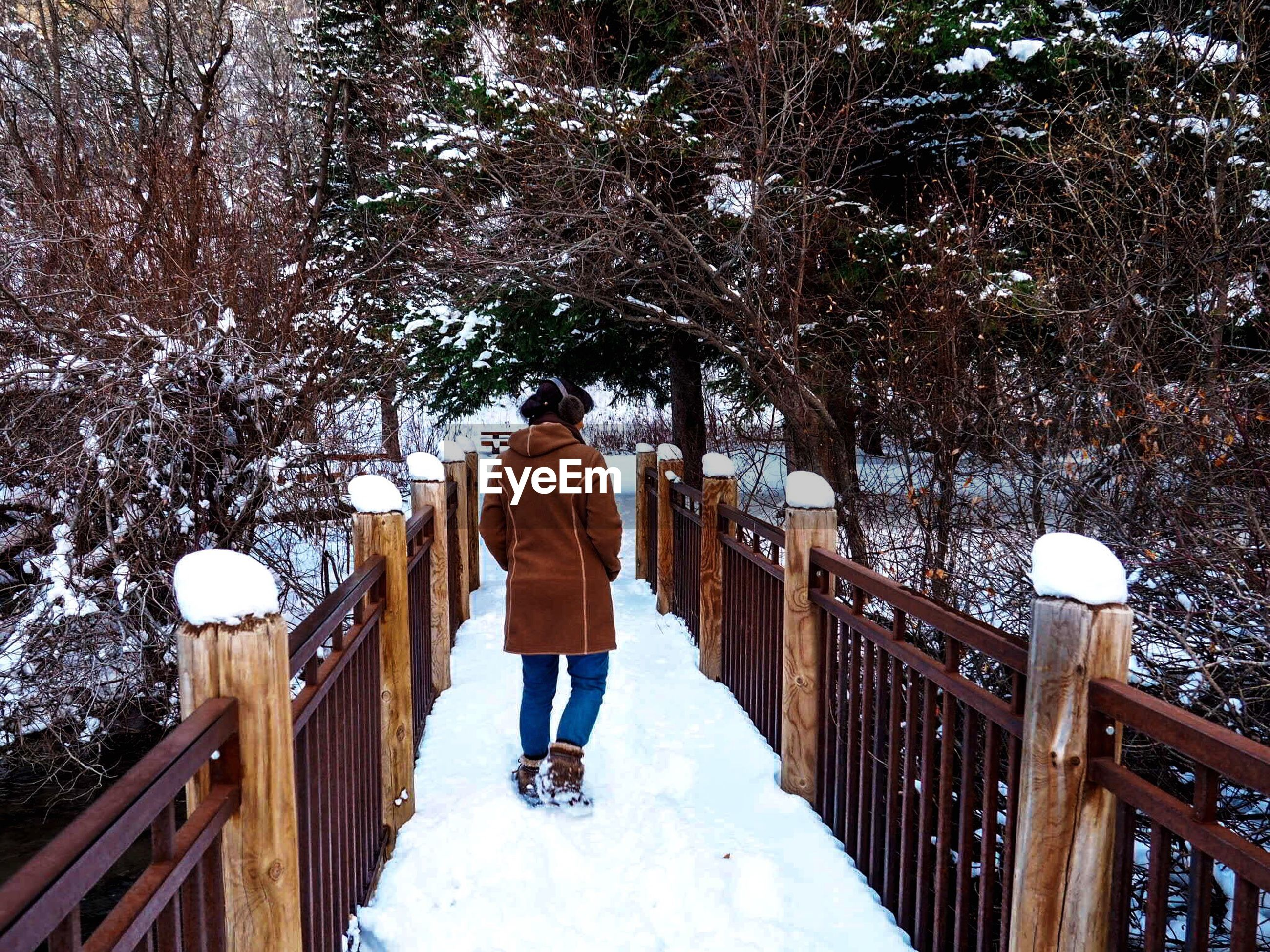 railing, full length, standing, one person, childhood, outdoors, leisure activity, winter, people, steps, snow, warm clothing, steps and staircases, cold temperature, nature, day, adult