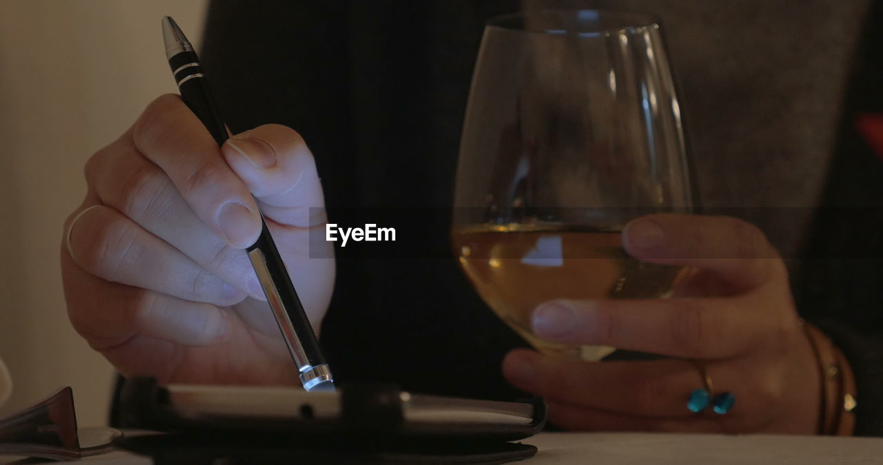 CLOSE-UP OF HAND HOLDING WINE GLASSES