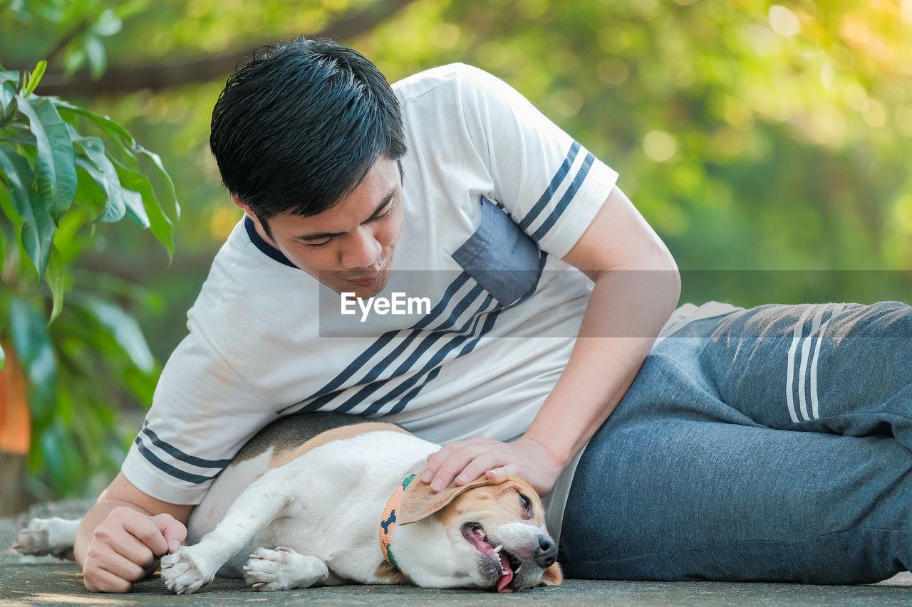 MIDSECTION OF MAN WITH DOG ON WOMAN