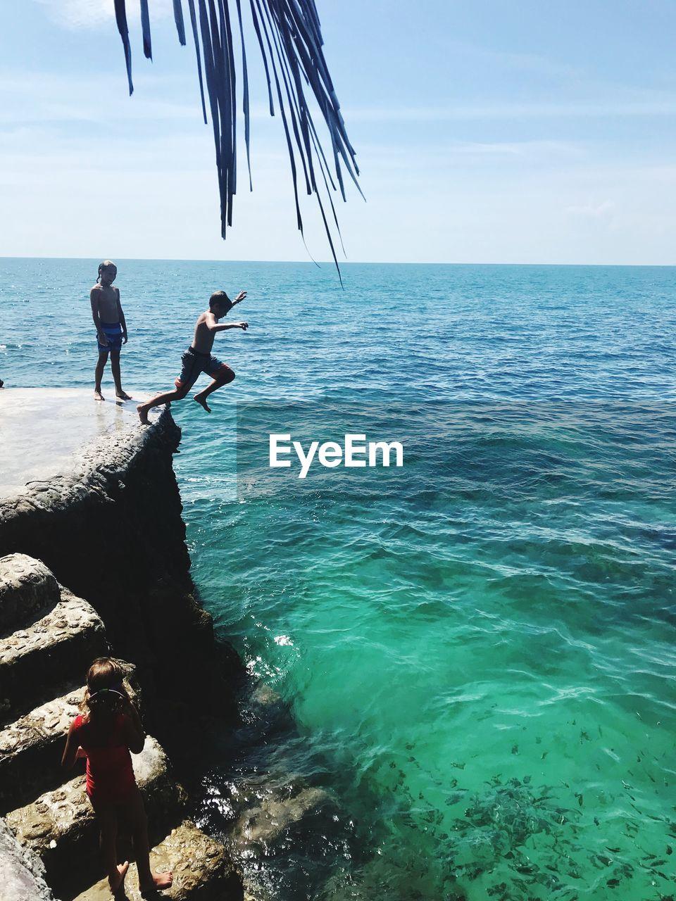PEOPLE AT SEA AGAINST SKY
