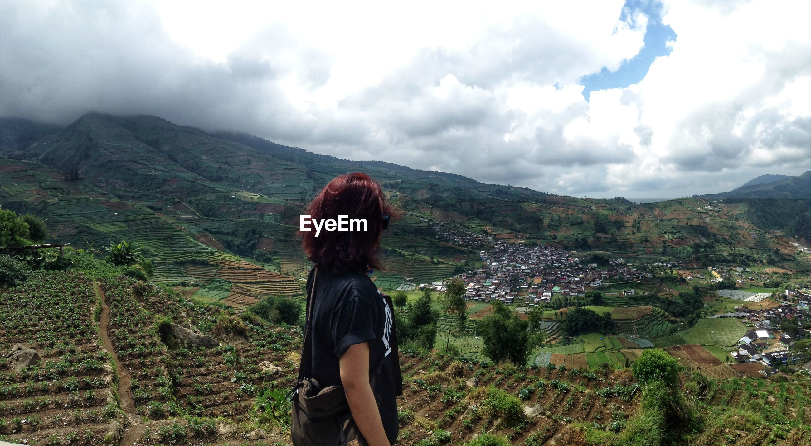 Side view of woman standing by mountains against cloudy sky
