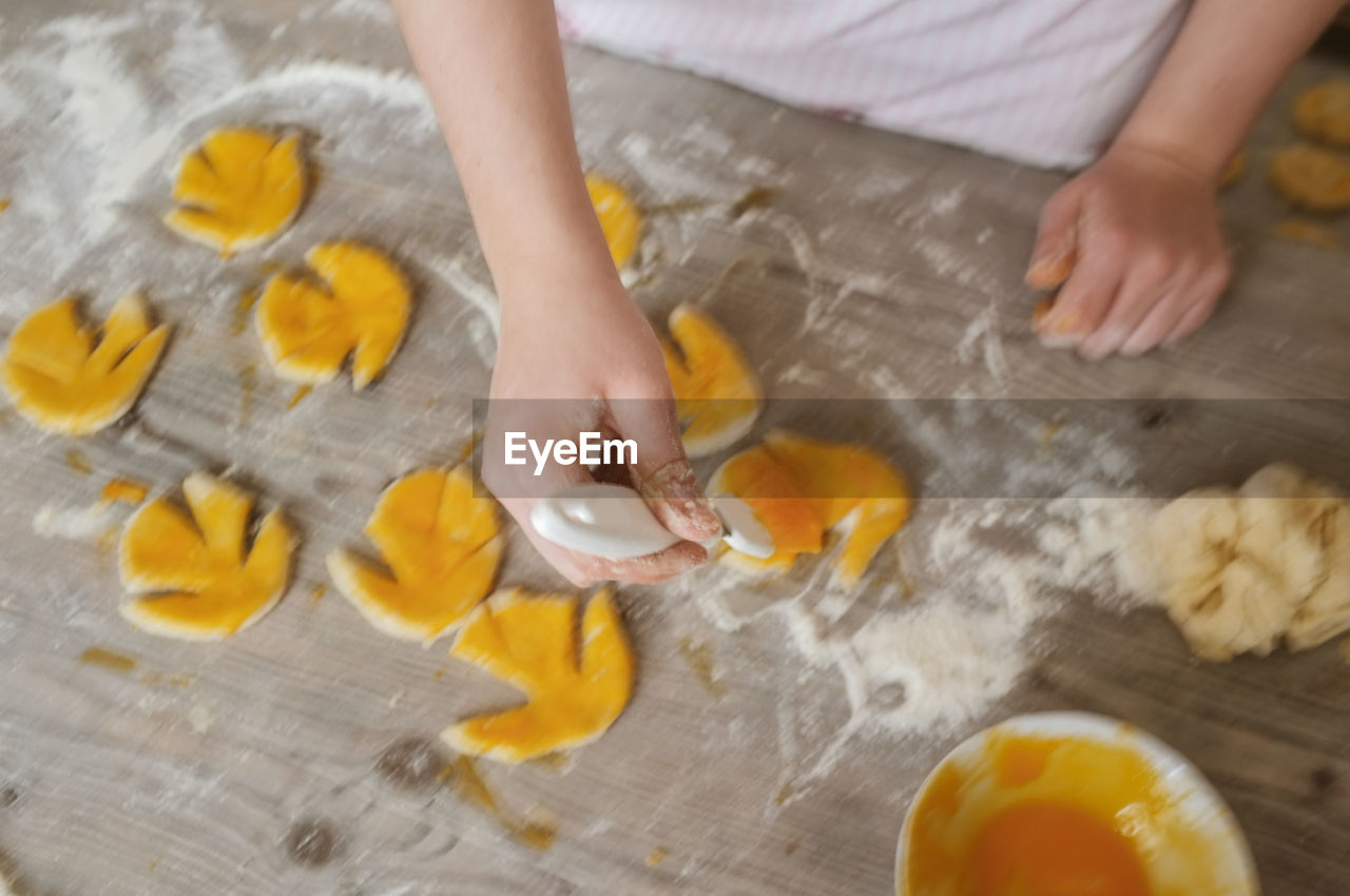 Cropped Image Of Hand Making Cookies On Table