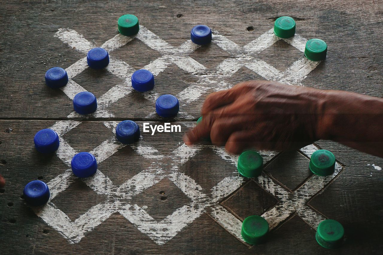 Man playing game of checkers on wooden board using bottle caps