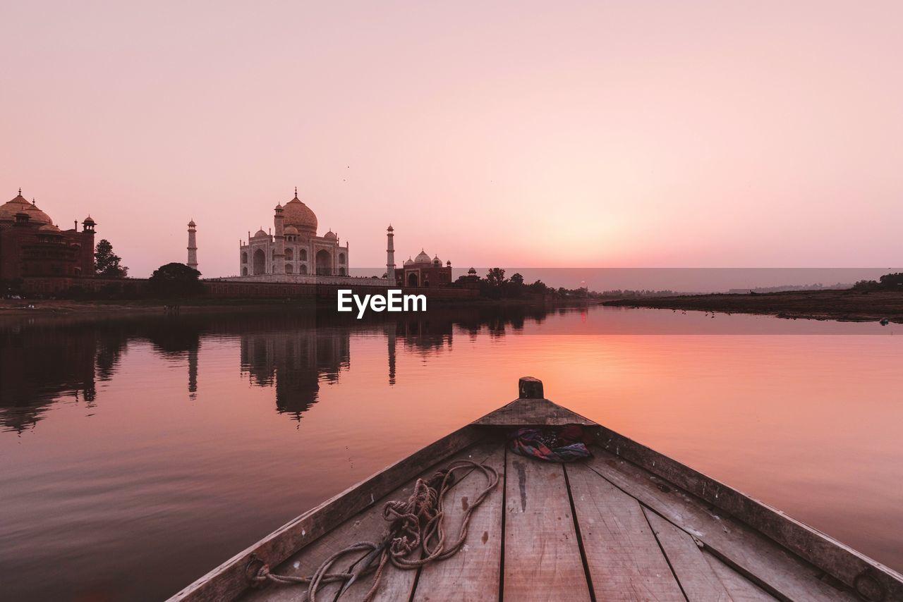 Boat in lake during sunset against taj mahal