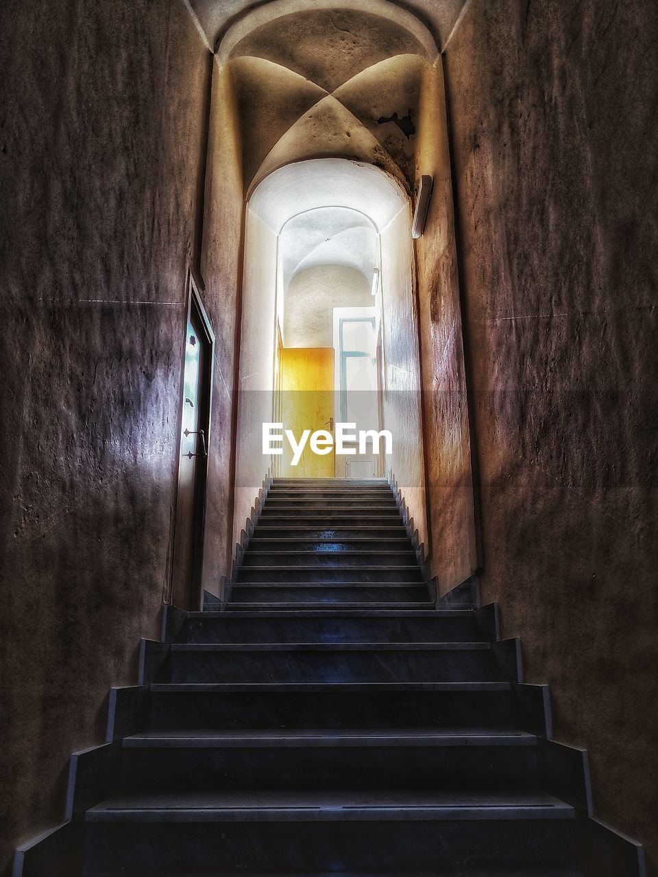 indoors, staircase, the way forward, architecture, direction, no people, arch, steps and staircases, built structure, low angle view, building, day, empty, wall - building feature, absence, diminishing perspective, old, door, illuminated, ceiling, light at the end of the tunnel