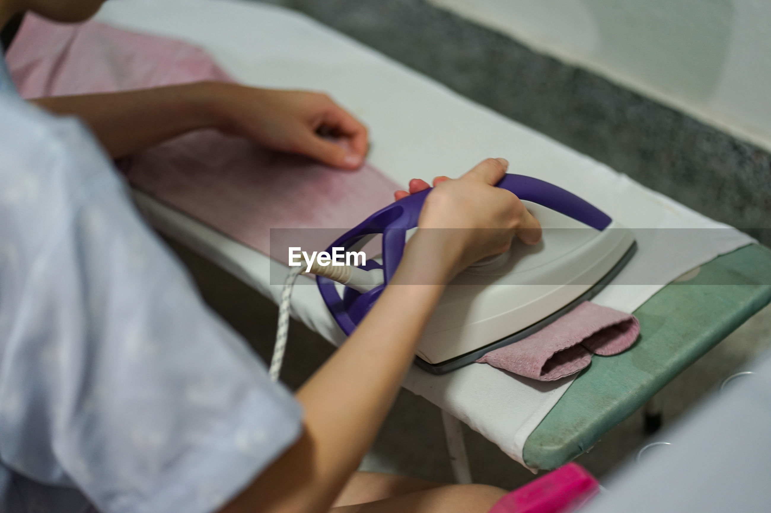 High angle view of woman ironing clothing