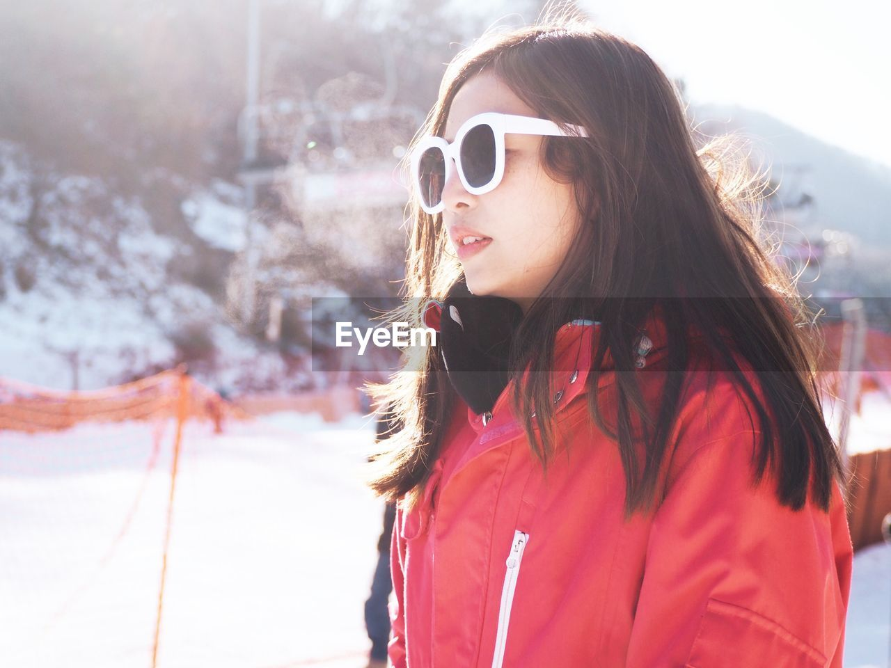 Young Woman Wearing Sunglasses While Standing On Snow Covered Field