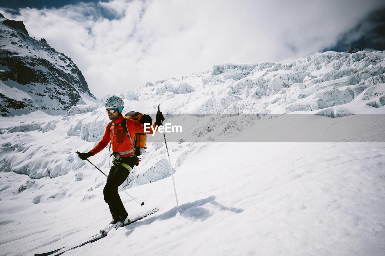 Man Skiing On Snow Covered Mountain Against Cloudy Sky