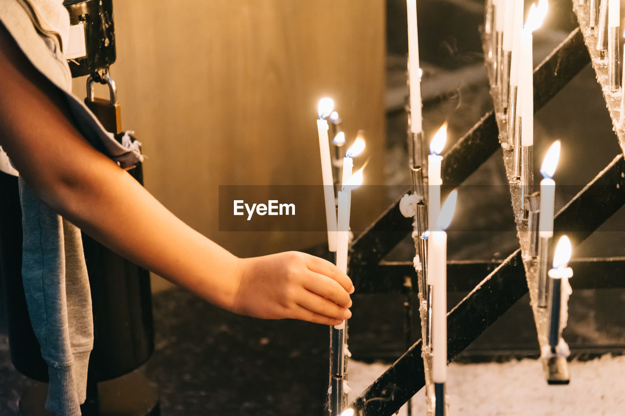 Close-Up Of Hand With Church Candles