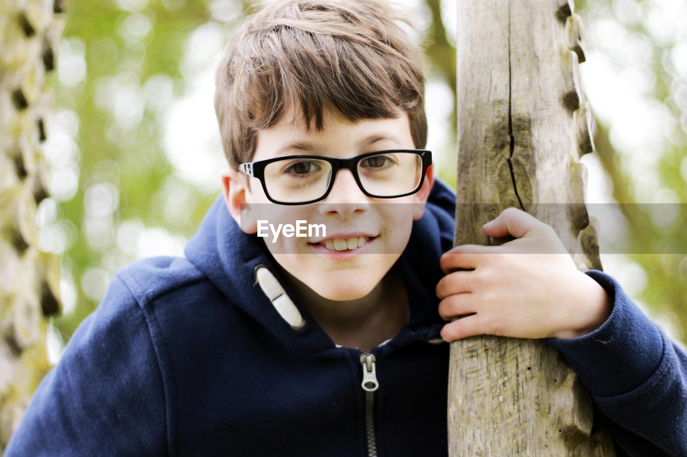 Portrait of boy wearing eyeglasses holding tree trunk