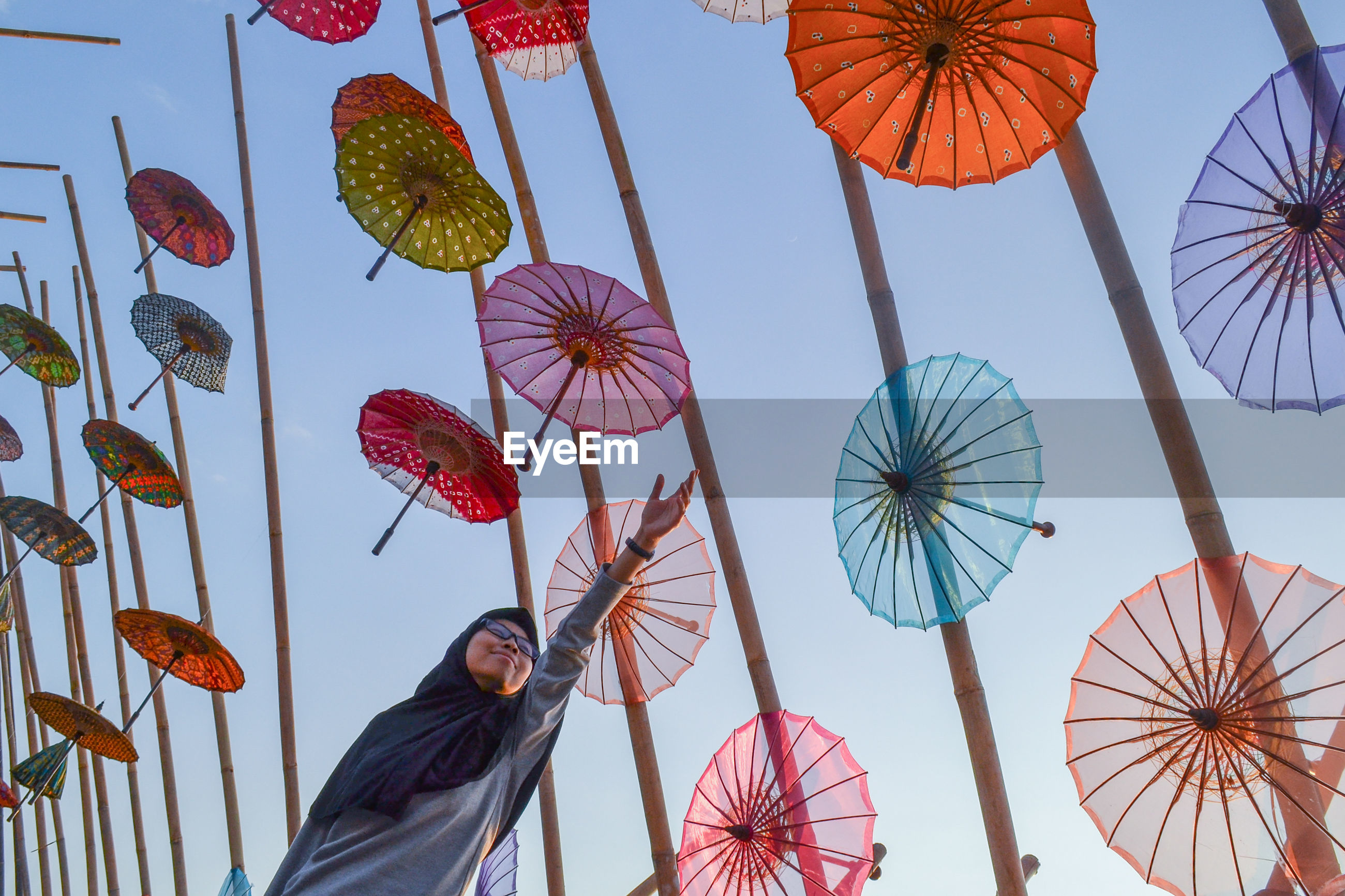 Low angle view of woman by umbrellas hanging against sky