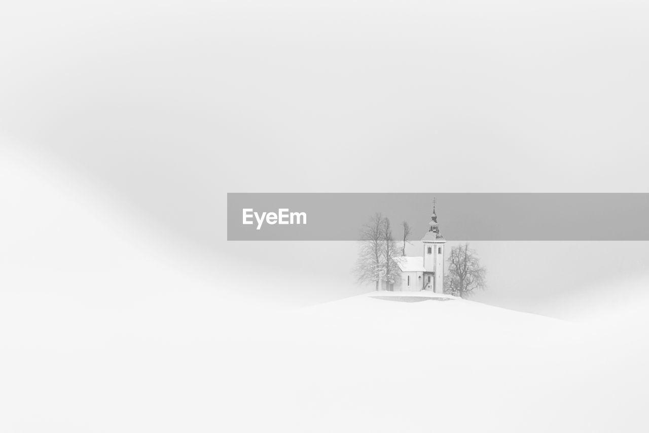 Church on snow covered field against clear sky
