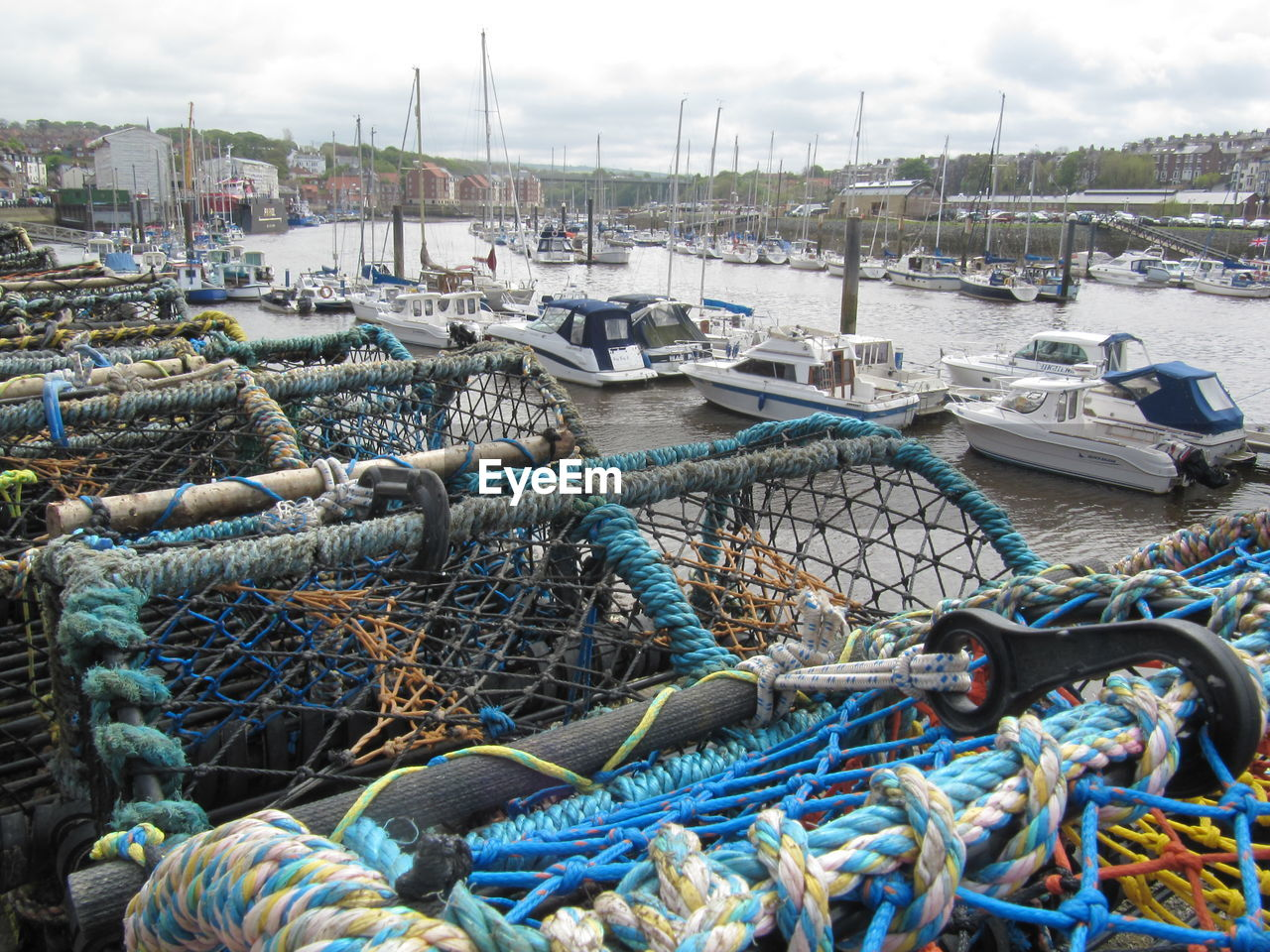 High Angle View Of Lobster Traps By Boats Moored In River