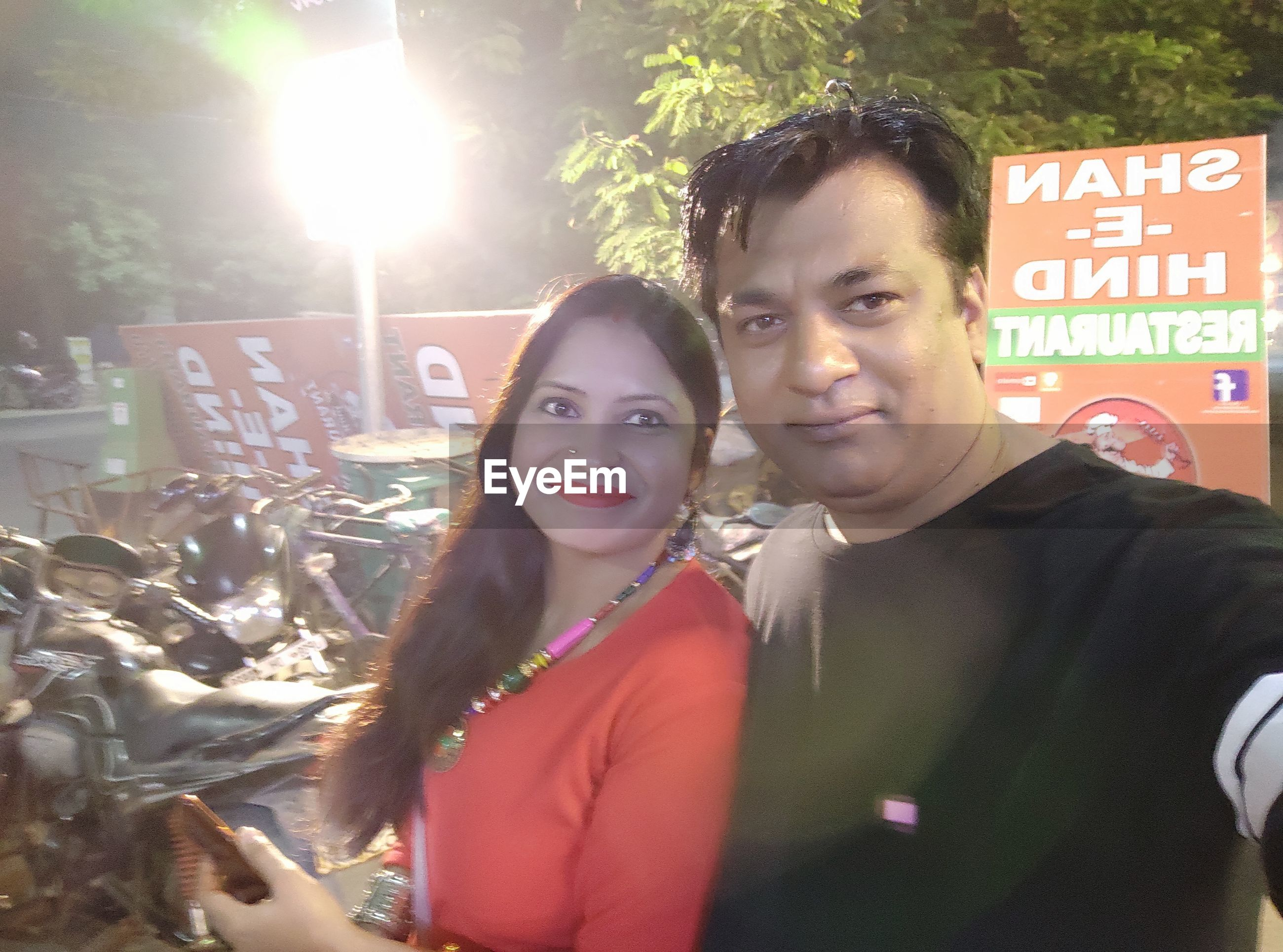 Portrait of smiling couple taking selfie while standing outdoors at night