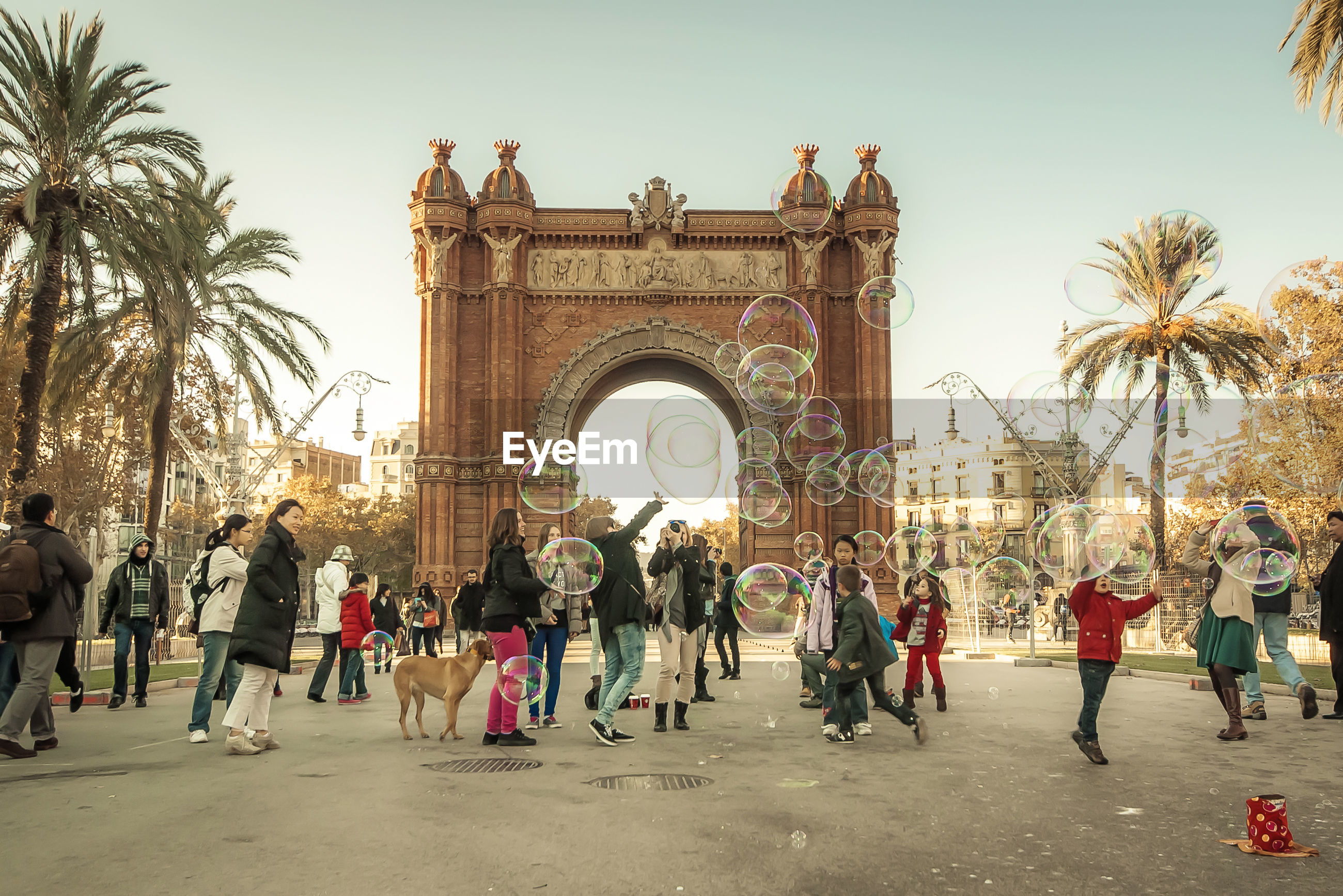 People playing with soap bubbles at arc de triomf against sky