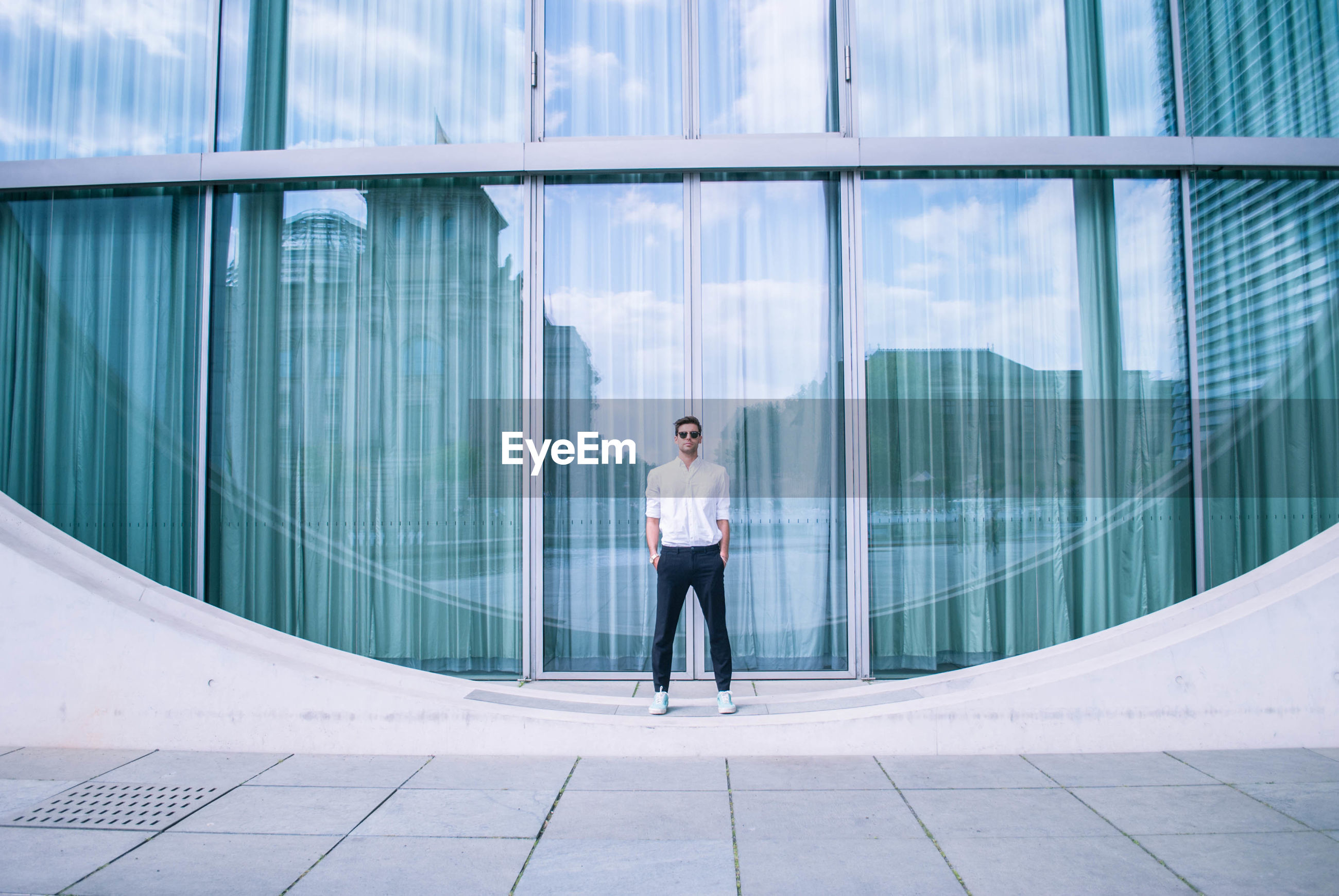 Full length of man standing by modern building