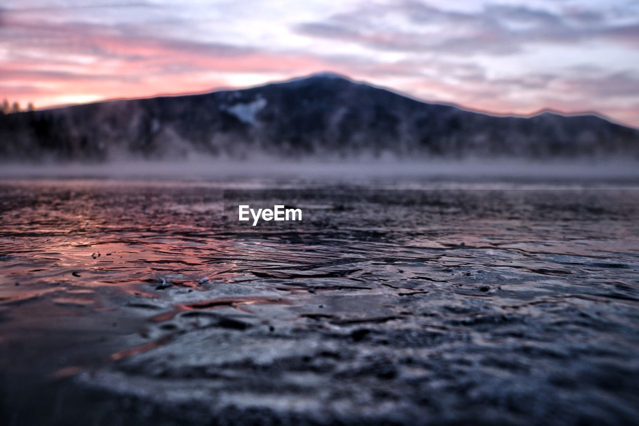 Scenic view of frozen lake and mountain against sky during sunrise