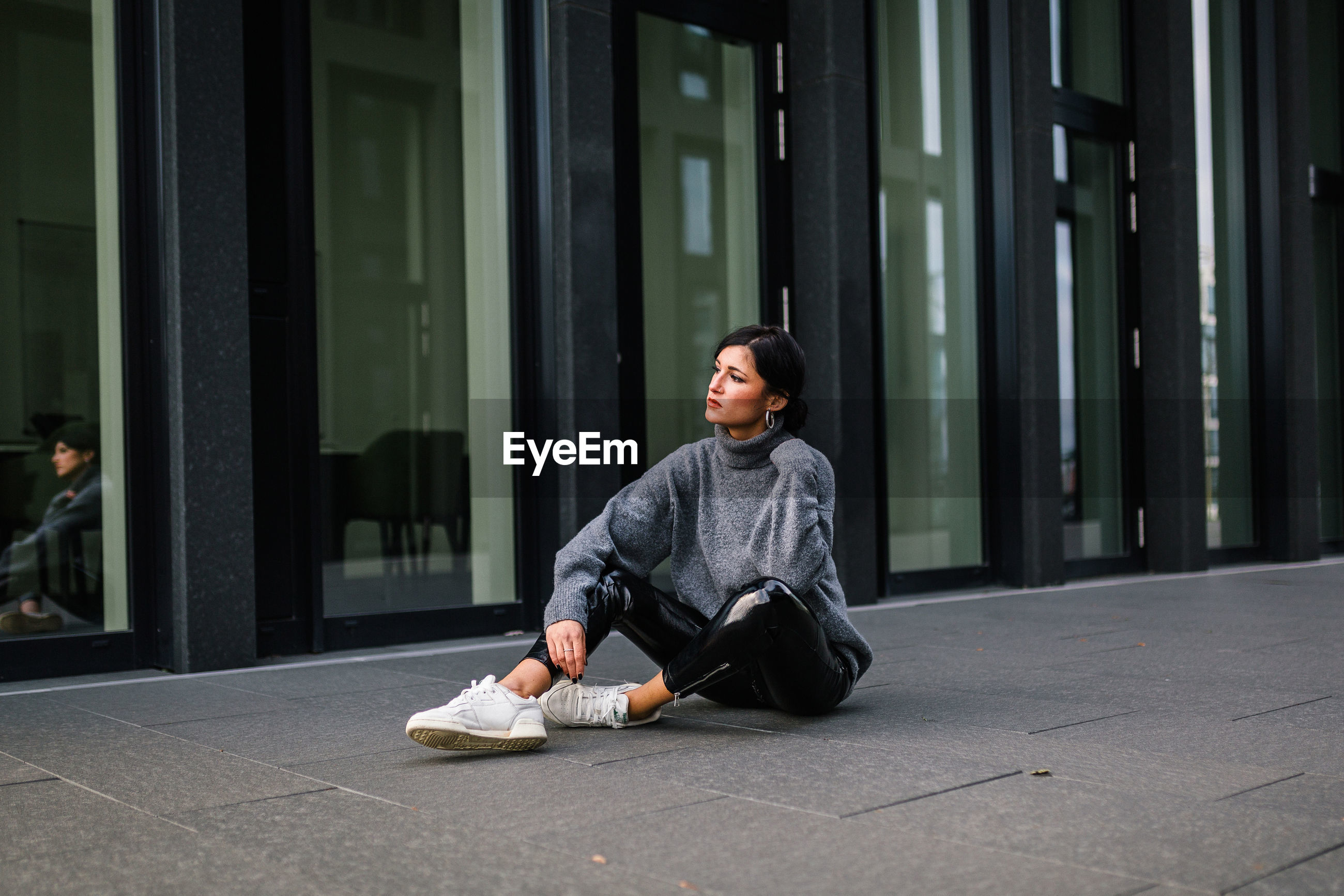PORTRAIT OF WOMAN SITTING ON FOOTPATH AGAINST BUILDING